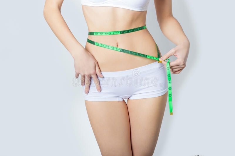 Young sports a beautiful slim woman measuring perfect shape nice hips, the concept of a healthy lifestyle on a white background stock image