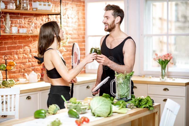 Sports couple eating healthy food on the kitchen at home. Young sports couple having a snack with vegetarian food drinking smoothie standing with rackets on the royalty free stock photos
