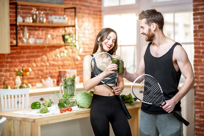 Sports couple eating healthy food on the kitchen at home royalty free stock photos