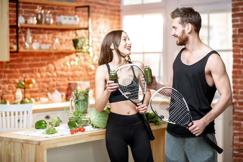 Sports couple eating healthy food on the kitchen at home stock photo