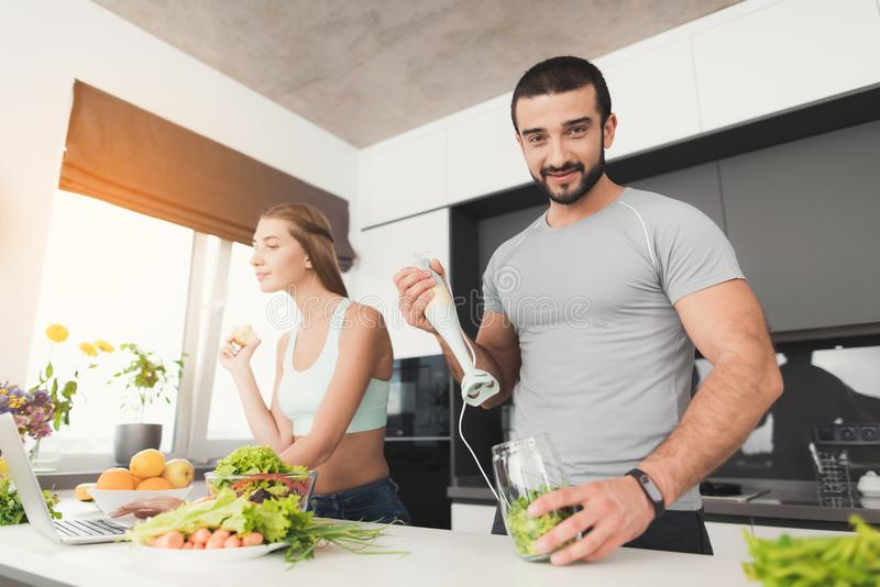 Young sports couple is preparing in the morning in the kitchen. A man is making a green vegetable cocktail. stock image