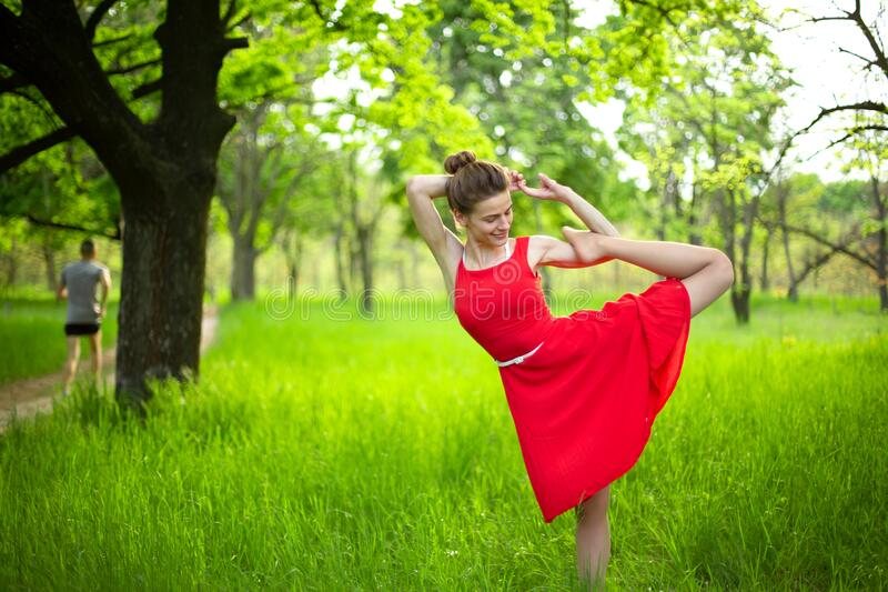 Young sports girl in a red dress practices yoga in a quiet green forest. Meditation and oneness with nature.  stock photo