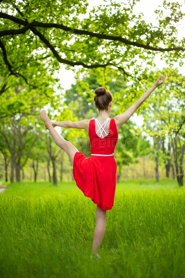 Young sports girl in a red dress practices yoga in a quiet green forest. Meditation and oneness with nature.  stock photos