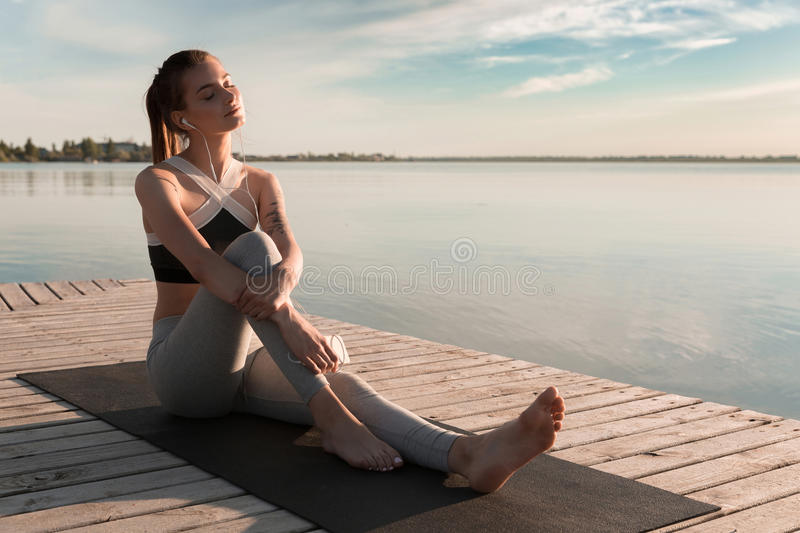 Young sports lady at the beach listening music with earphones. Picture of young sports lady at the beach listening music with earphones. Eyes closed stock photography