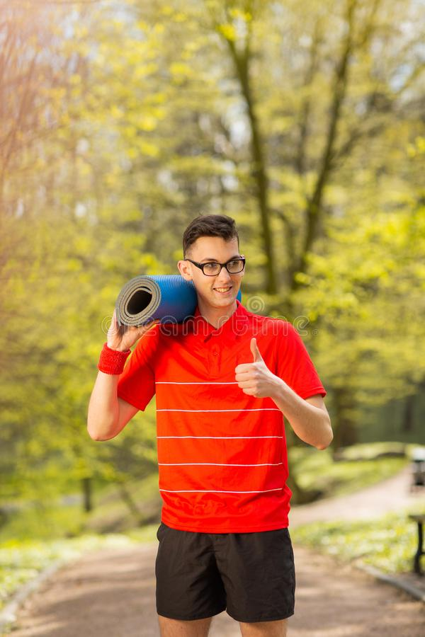 Young sports man in red t-shirt posing in a spring park with a blue yoga mat. His hands shows class.  stock image