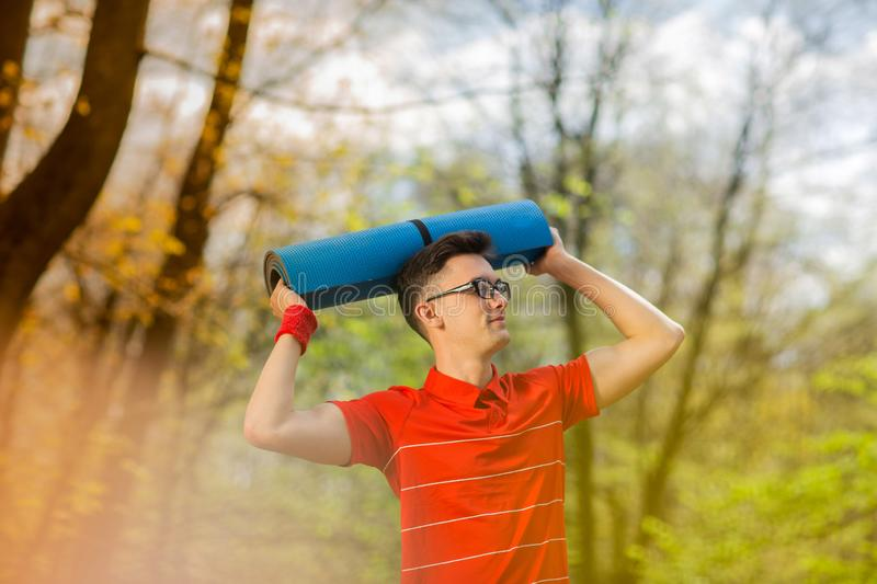 Young sports man in red t-shirt posing in a spring park with a blue yoga mat. He holds a yoga mat over his head.  stock photo