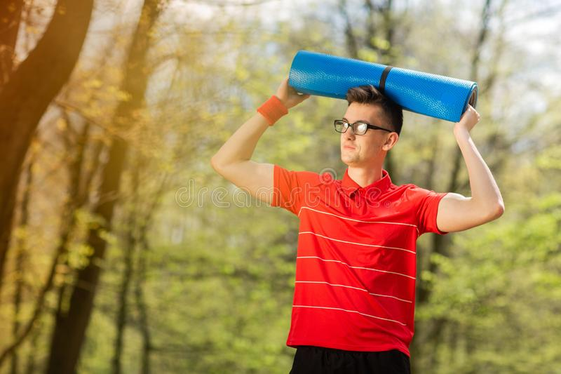 Young sports man in red t-shirt posing in a spring park with a blue yoga mat. He holds a yoga mat over his head.  royalty free stock image