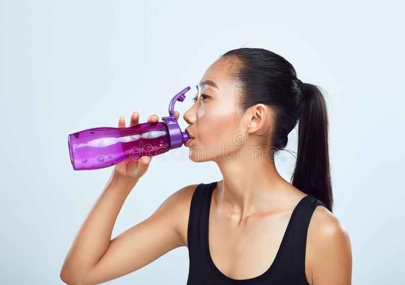 Young sports woman drinks bottled water royalty free stock photography