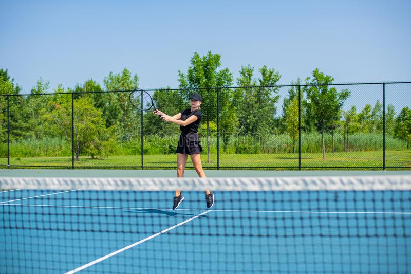 Young sports woman playing tennis on the blue tennis court stock images