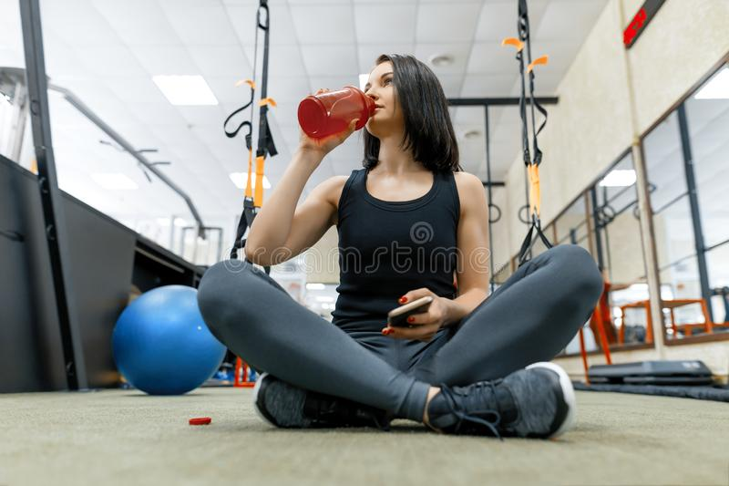 Young sports woman resting on the floor after exercises in gym, drinking water reading smartphone. Fitness, sport, training, royalty free stock photos