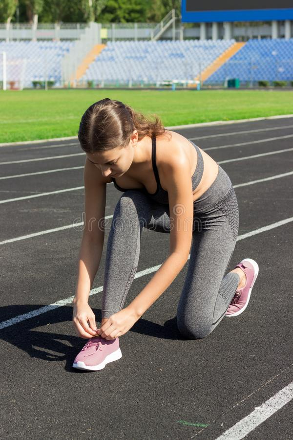 Young sportsgirl tying her shoelaces on run track in stadium sport and fitness concept stock image