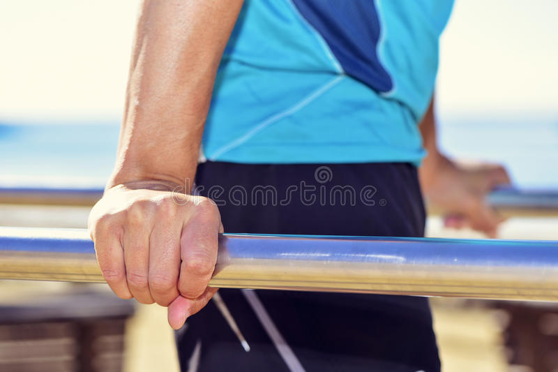 Young sportsman doing dips in parallel bars royalty free stock photo