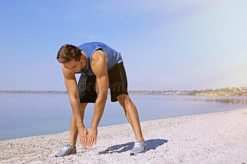Young sportsman doing exercises on riverside stock photography