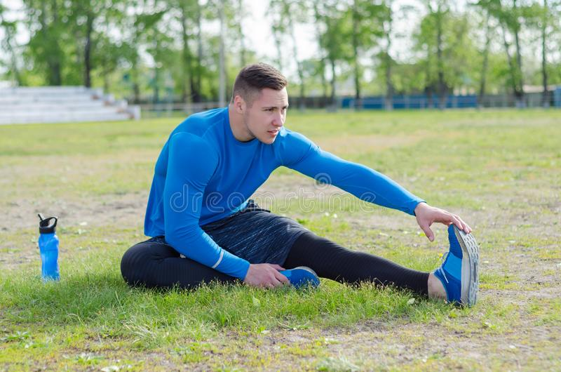 Portrait of a young sportsman doing stretching exercise, preparing for morning training stock photos