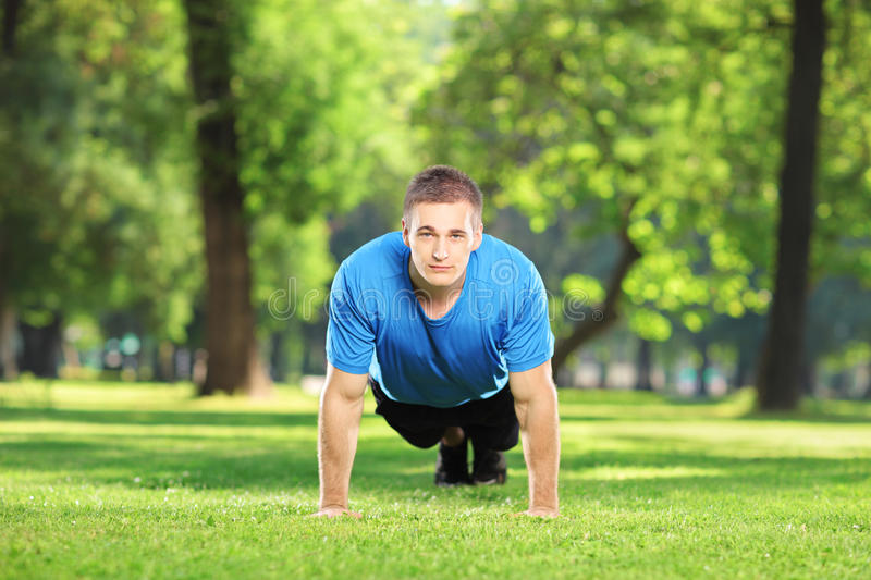 Young sportsman exercising in a park