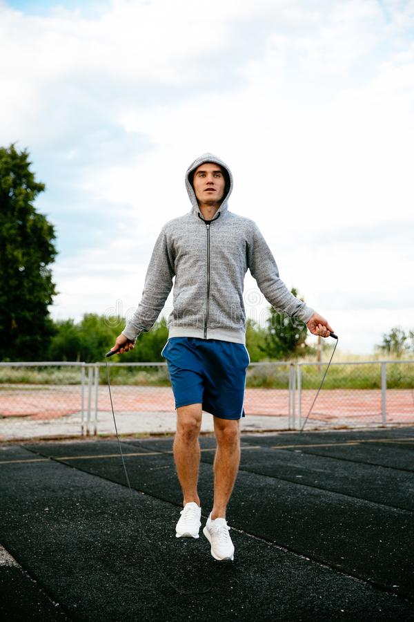 Young sportsman exercising with skipping rope. Full length portrait of a handsome sportsman jumping with skipping rope at the stadium royalty free stock photo