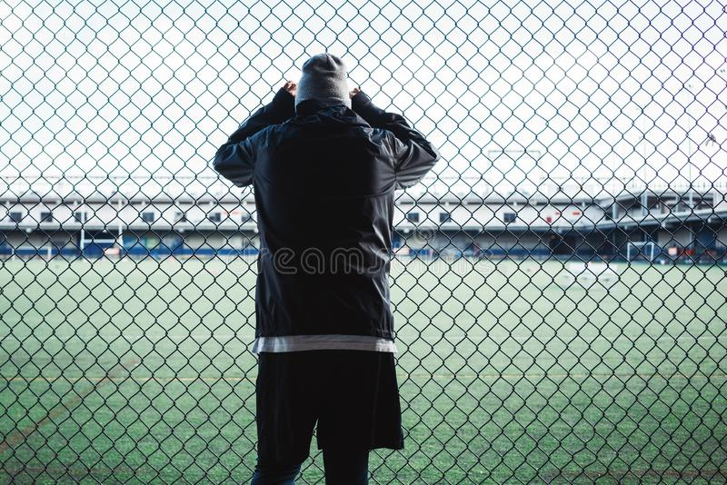 Young sportsman resting after sport excursion run near the fence. Concept royalty free stock image