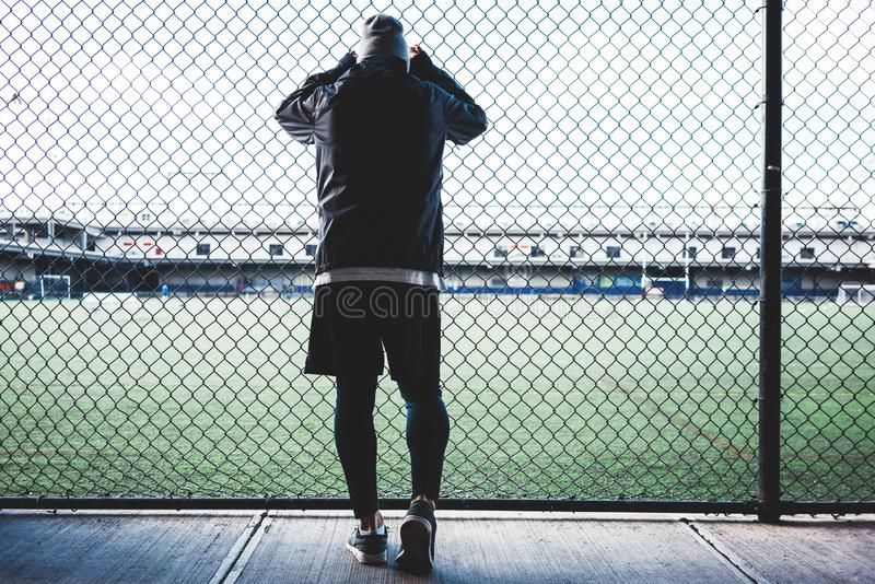 Young sportsman resting after strong and fast run near the fence. Concept. Tired athlete man leaned and holding on to the rabitz fence. Young sportsman resting royalty free stock image