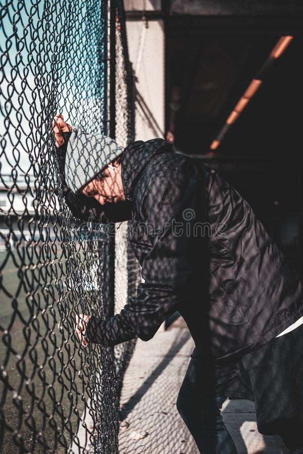 Young sportsman resting after strong and fast run near the fence stock images