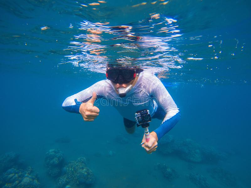 Young sportsman in snorkeling mask shows thumb underwater. royalty free stock images
