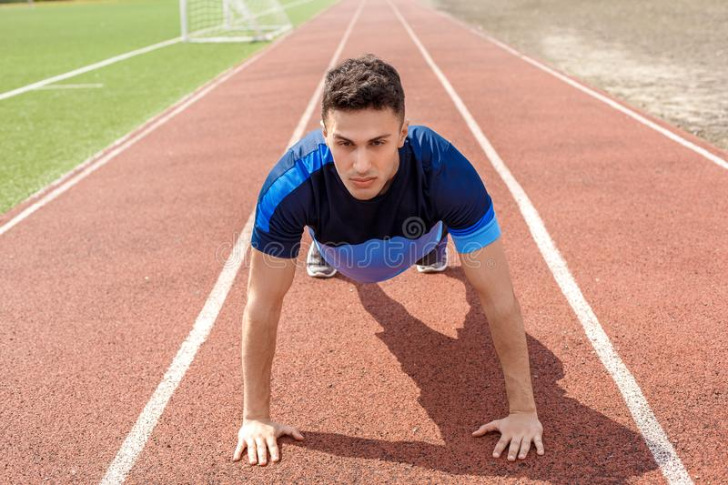 Young man on stadium outside standing on arms doing push-ups concentrated royalty free stock photography