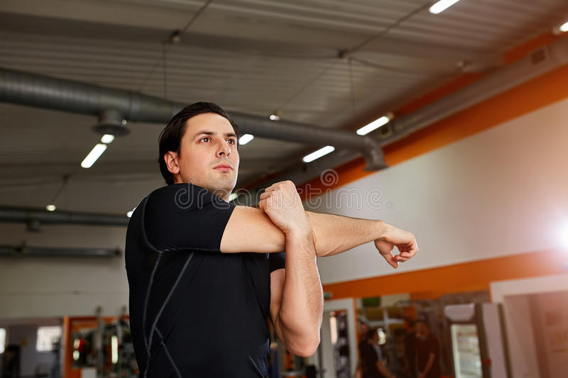 Young sportsman standing indoor and stretching triceps before gym workout. Athlete man in the black sportwear, t-shirt. Horizontal photo. Healthy lifestyle stock photography