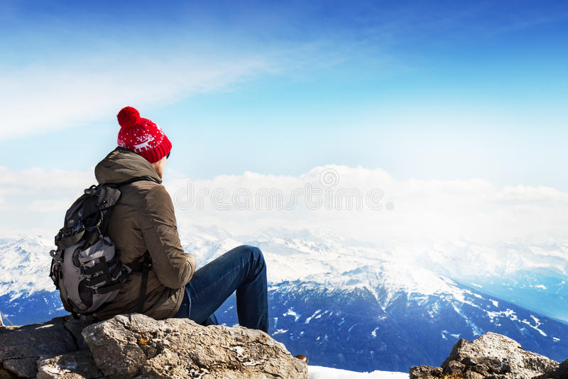 Young sportsman or traveler sitting on stone and looking on horizon. Mountain range on background. Beautiful Landscape. Horizontal. Travel Concept royalty free stock photography