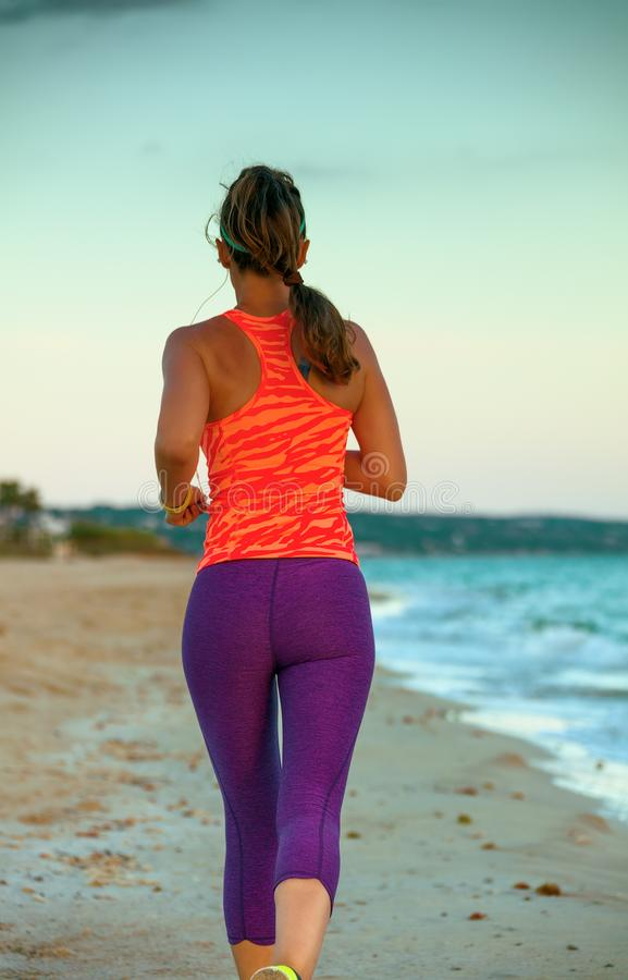 Young sportswoman on beach in evening jogging royalty free stock photo