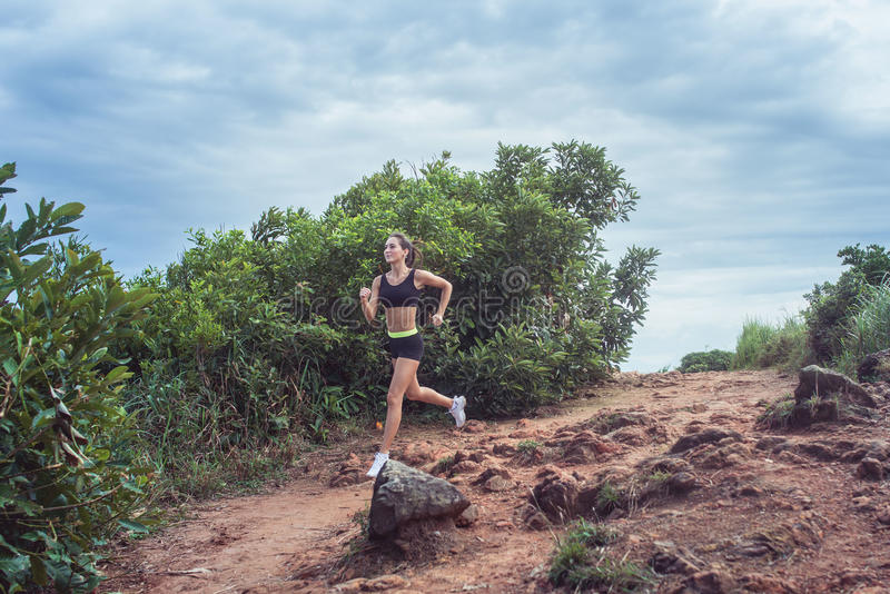 Young sportswoman cross country running on dirty rocky footpath in mountains in summer. Fit girl jogging outdoors in royalty free stock photography