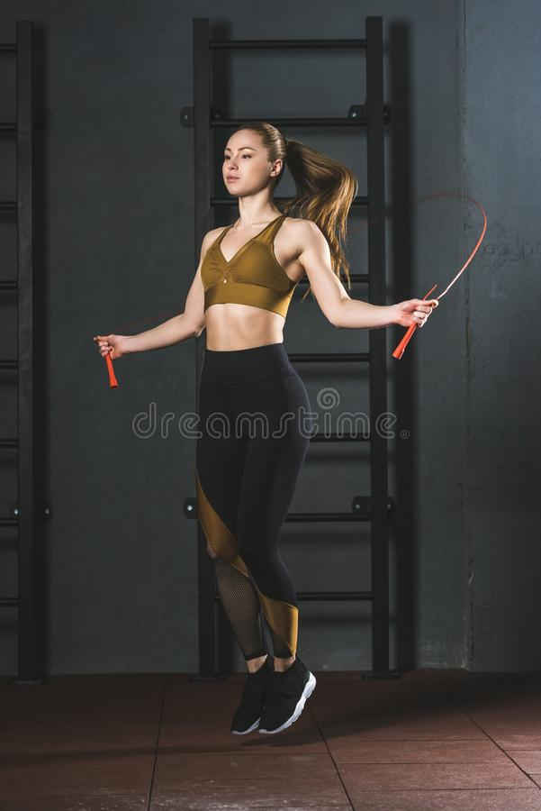 Young sportswoman doing jump rope workout. In gym stock photo