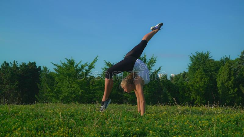 Young sportswoman doing workout outdoors. Blonde woman doing exercises for flexible and coordination in park with beautiful fresh green grass and summer nature stock photo