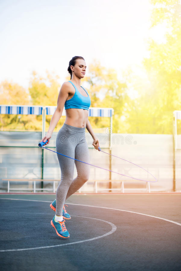 Young sportswoman exercising with skipping rope on stadium stock photo