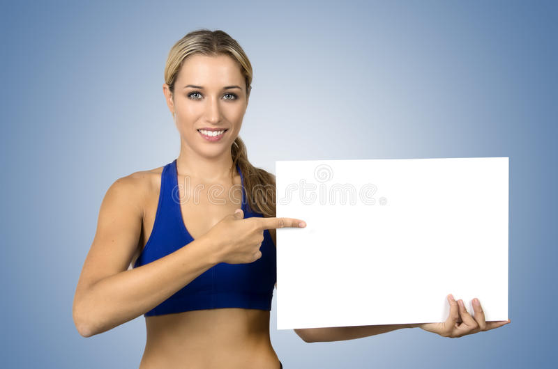 Young sportswoman holding blank board and pointing on it royalty free stock photo