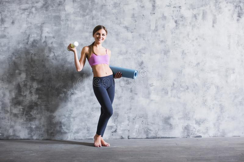 Young sportswoman holding yoga mat indoors. stock photography