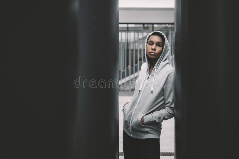 Young sportswoman in hood posing with hands in pockets and looking at camera royalty free stock photo