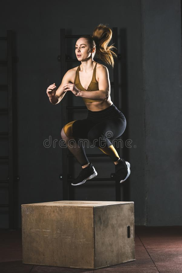 Young sportswoman jumping on wooden block. In gym stock photos