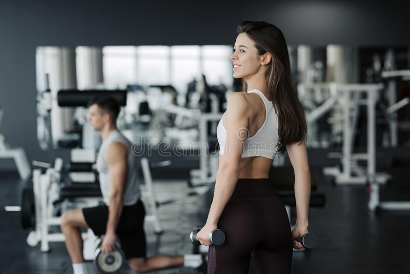 Young sportswoman lifting weights in gym wearing sportswear with her boyfriend on background royalty free stock photography