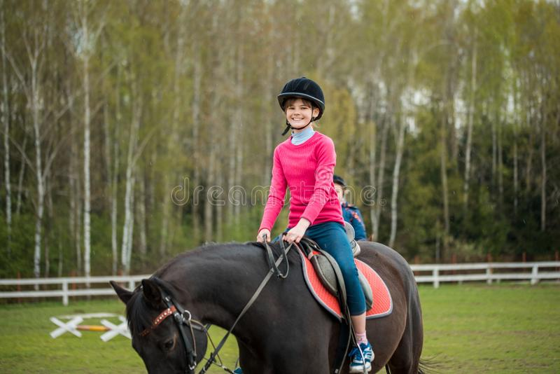 Young sportswoman riding horse in equestrian show jumps competition. Teenage girl ride a horse royalty free stock image