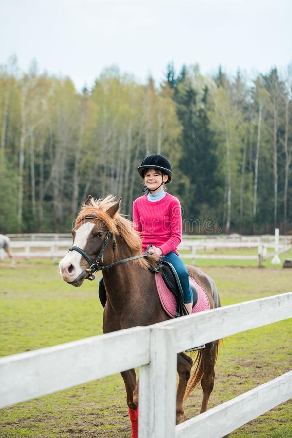 Young sportswoman riding horse in equestrian show jumps competition. Teenage girl ride a horse stock image