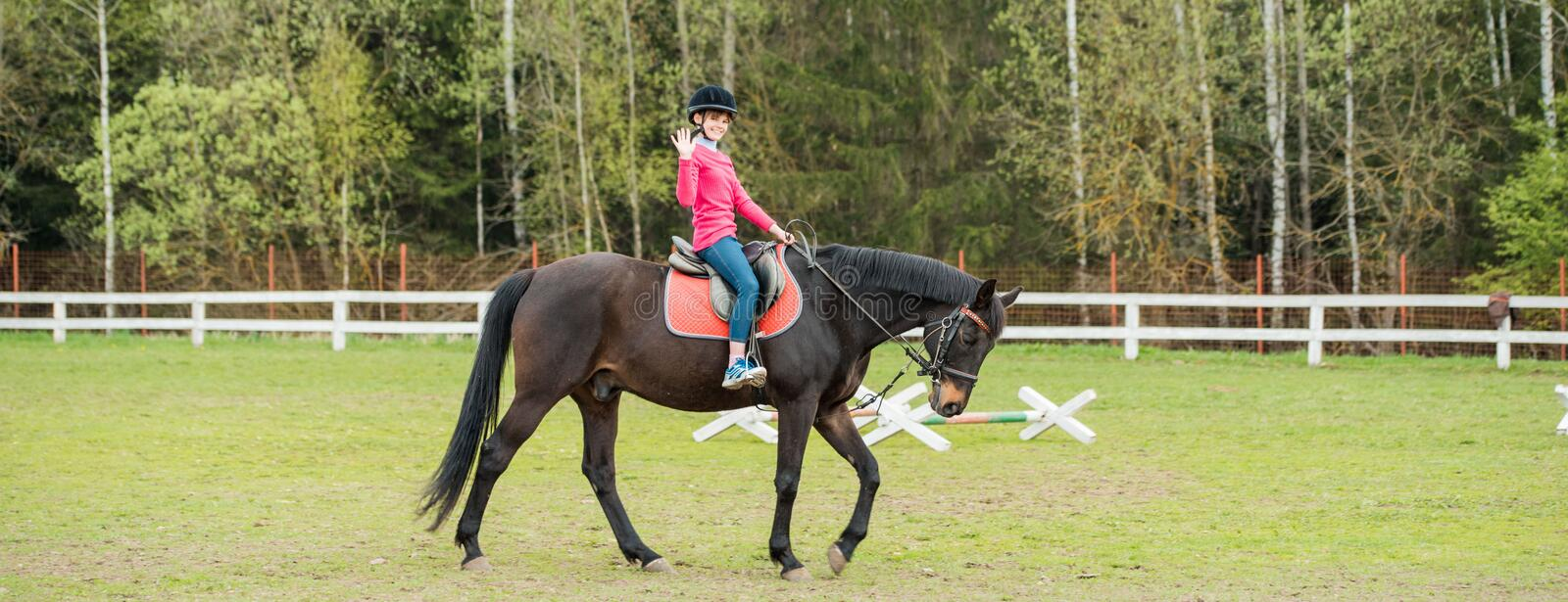 Young sportswoman riding horse in equestrian show jumps competition. Teenage girl ride a horse stock photography
