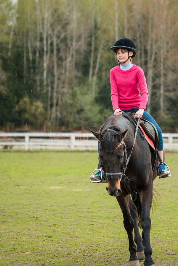 Young sportswoman riding horse in equestrian show jumps competition. Teenage girl ride a horse stock images