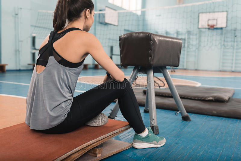 Young sportswoman sitting and looking at distance in sports center royalty free stock image
