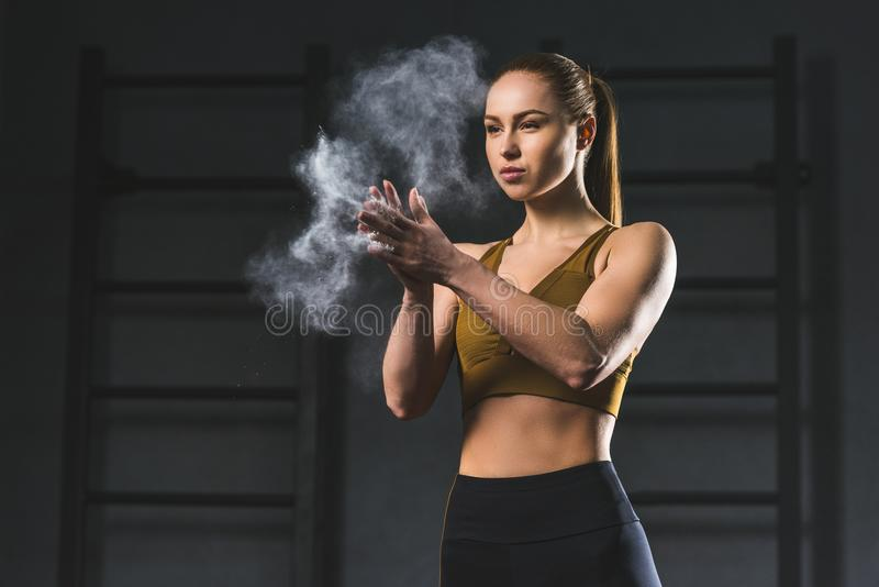 Young sportswoman spreading chalk powder in hands for exercising. In sports hall royalty free stock images