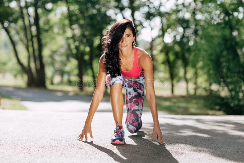 Young sportswoman stretching and preparing to run. royalty free stock photography