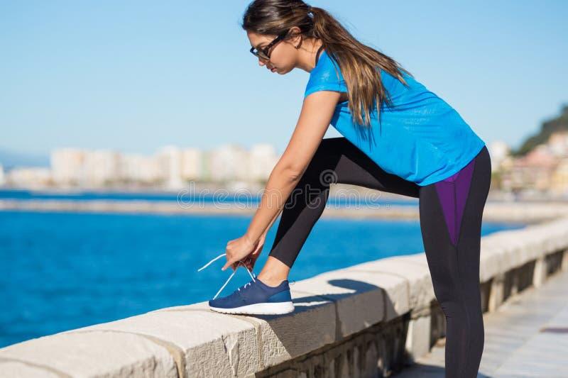 Young sportswoman tying shoelace outside stock image