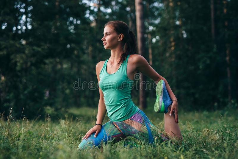 Young sportswoman warming-up before workout doing stretching exercises sitting on grass in park stock images
