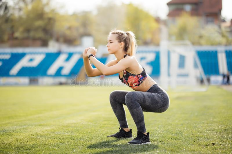 Young sportswoman warming up before workout doing stretching sit-ups exercises sitting on grass in park royalty free stock image
