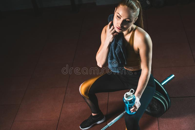 Young sportswoman wiping neck by towel and sitting on barbell. In gym stock photography