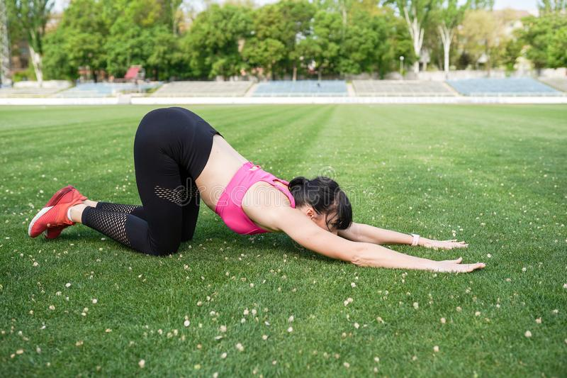 Young sportwoman stretching muscles over green background with copy space. Sunny day health lifestyle.  stock photos