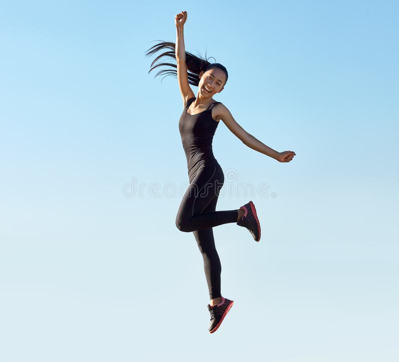 Young sporty asian woman happy jumping outdoors royalty free stock image